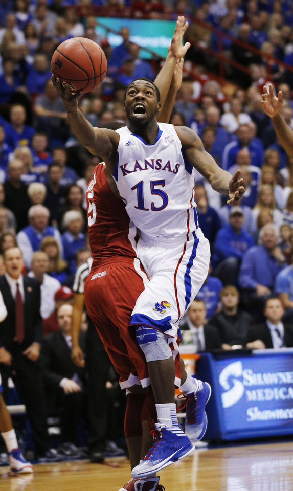 Kansas guard Elijah Johnson (15) charges into Oklahoma guard Je\'lon Hornbeak (5) during the first half of an NCAA college basketball game in Lawrence, Kan., Saturday, Jan. 26, 2013. (AP Photo/Orlin Wagner)