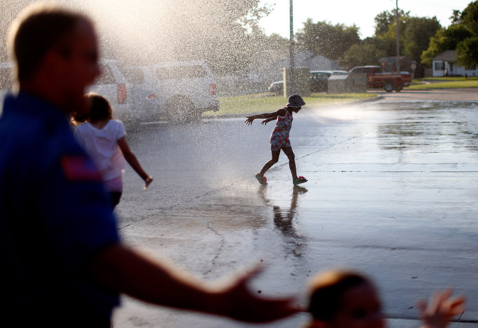Photo -  Children run through water from a fire hose as cancer patients, along with their family, from ProCure got a chance to have dinner and tour the Warr Acres fire station on Wednesday, July 24, 2013. Photo by Bryan Terry, The Oklahoman