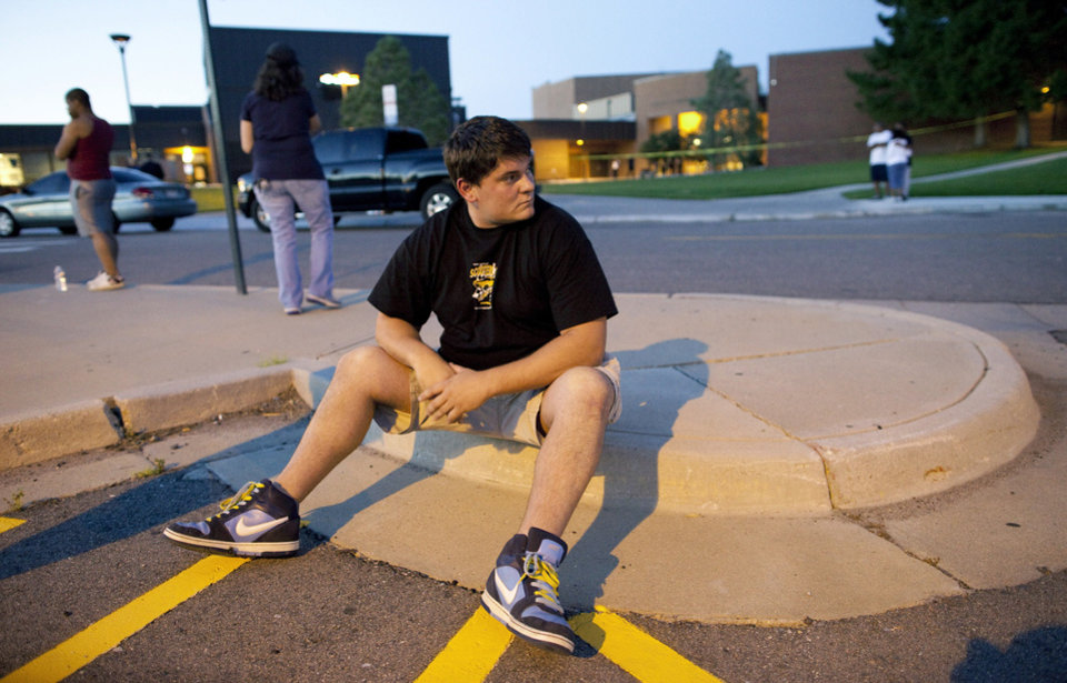 Photo - Eyewitness Chandler Brannon, 25, sits outside Gateway High School where witnesses were brought for questioning after a shooting at a movie theater showing the Batman movie