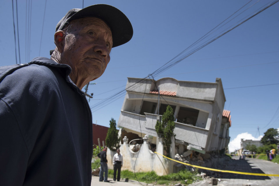 Photo - A man stands close to homes that collapsed during an earthquake in San Pedro, Guatemala, Monday, July 7, 2014. A magnitude-6.9 earthquake on the Pacific Coast jolted a wide area of southern Mexico and Central America Monday. (AP Photo/Oliver de Ros)