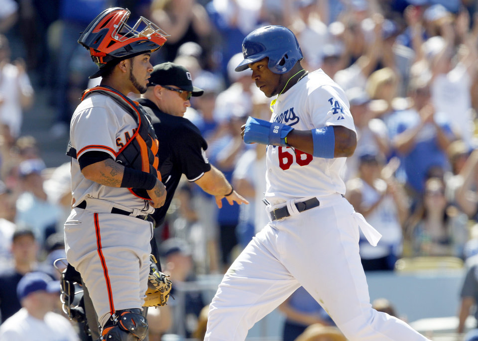 Photo - Los Angeles Dodgers' Yasiel Puig (66) scores with San Francisco Giants catcher Hector Sanchez, left, and home plate umpire Mark Carlson, center, looking on after a single hit by Dodgers' Matt Kemp in the sixth inning of a baseball game on Saturday, May 10, 2014, in Los Angeles. (AP Photo/Alex Gallardo)