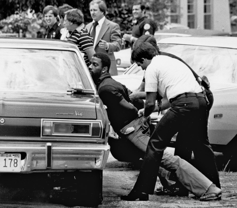 FILE - In this May 18, 1979 file photo, police handcuff a suspect during a drug raid in Miami. Police said eight were arrested and marijuana was seized. On the occasion of  �Legalization Day,� Thursday, Dec. 6, 2012, when Washington�s new law takes effect, AP takes a look back at the cultural and legal status of the �evil weed� in American history. (AP Photo/Al Diaz, File)