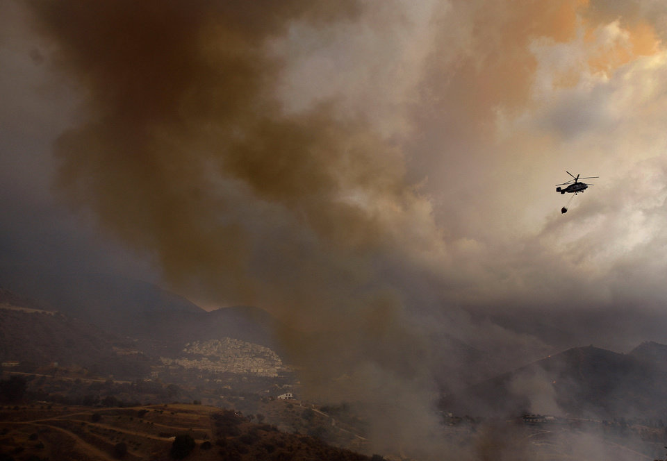 Photo -   A firefighting helicopter transporting a water bucket heads towards a fire in Ojen, southern Spain, Friday, Aug. 31, 2012. Spanish officials say some 4,000 people have been evacuated from their houses as a wildfire abetted by strong winds spread rapidly through hills around the popular southern tourist city of Marbella. (AP Photo/Sergio Torres)