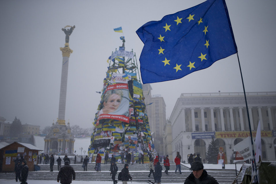 Pro-European Union activists walk as a EU flag flies over the Independence Square with a poster of of jailed Ukrainian former Prime Minister Yulia Tymoshenko on a metal base of destroyed Christmas tree in KIev, Ukraine, Monday, Dec. 9, 2013. Dozens of riot police in full gear have moved into the center of the Ukrainan capital where opposition activists have been occupying a city administration building and a central square. (AP Photo/Alexander Zemlianichenko)