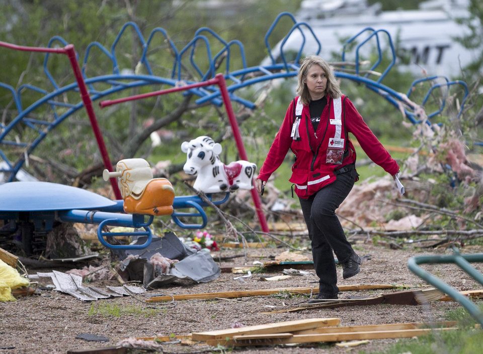 Photo -   Jill Orton, executive director of the Loess Hills chapter of the Red Cross, walks through a wrecked playground as she surveys damage in Thurman, Iowa, Sunday, April 15, 2012. A large part of the town in the western part of the state was destroyed Saturday night, possibly by a tornado, but no one was injured or killed. Fremont County Emergency Management Director Mike Crecelius said about 75 percent of the 250-person town was destroyed. (AP Photo/Nati Harnik)
