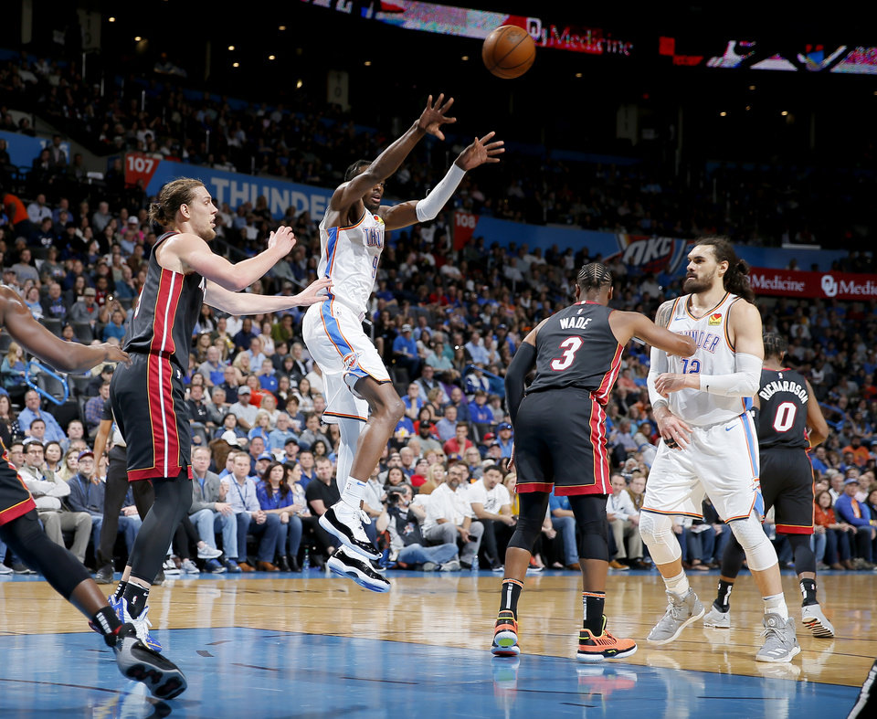 Photo - Oklahoma City's Jerami Grant (9) passes the ball from between Miami's Kelly Olynyk (9) and Dwyane Wade (3) during an NBA basketball game between the Oklahoma City Thunder and the Miami Heat at Chesapeake Energy Arena in Oklahoma City, Monday, March 18, 2019. Photo by Bryan Terry, The Oklahoman
