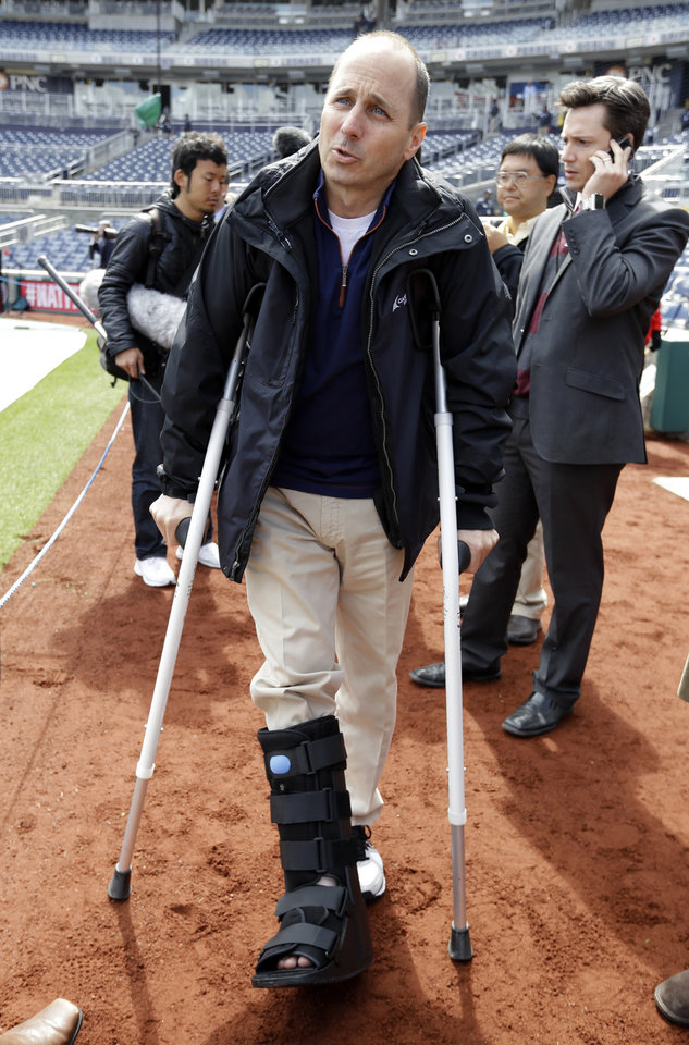 Photo - New York Yankees general manager Brian Cashman stands on crutches due to a skydiving injury, before an exhibition baseball game against the Washington Nationals at Nationals Park Friday, March 29, 2013, in Washington. (AP Photo/Alex Brandon)