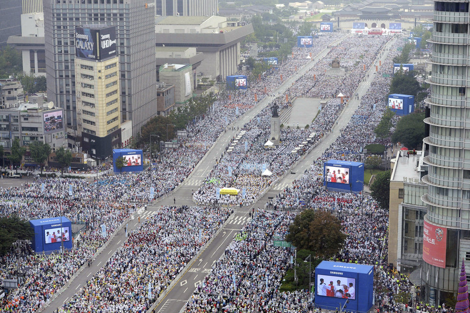 Photo - The faithful gather during the beatification mass of Paul Yun Ji-Chung and his 123 martyr companions in Seoul, South Korea, Saturday, Aug. 16, 2014. Pope Francis beatified 124 Korean martyrs on Saturday, telling hundreds of thousands of people who turned out for his open-air Mass that their ancestors' willingness to die rather than renounce their faith two centuries ago was a model for Asian missionaries today. (AP Photo/Korea Pool via Yonhap) KOREA OUT