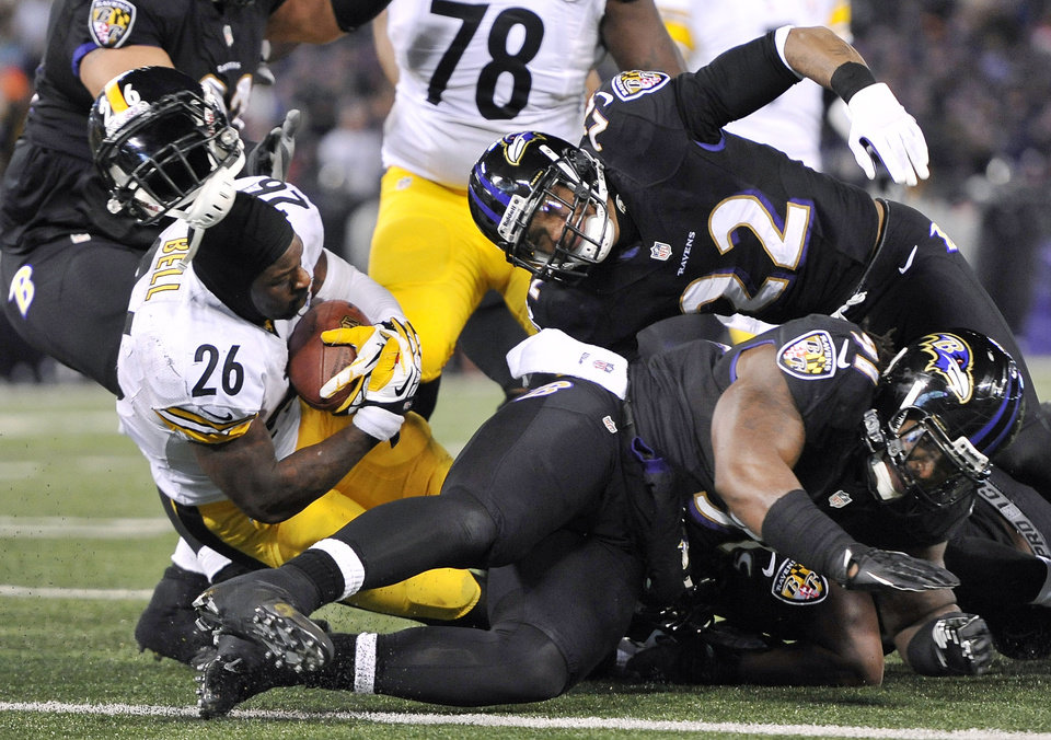 Photo - Pittsburgh Steelers running back Le'Veon Bell (26) loses his helmet after a collision as he tries to score a touchdown in the second half of an NFL football game against the Baltimore Ravens, Thursday, Nov. 28, 2013, in Baltimore. Bell left the field with an injury and the touchdown attempt was no good. (AP Photo/Gail Burton)