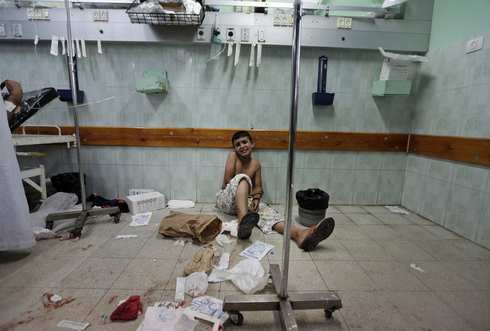 Photo - A Palestinian boy who was wounded in an Israeli strike on a house in Beit Lahiya, northern Gaza Strip, sits on the floor as he waits to be treated at the emergency room of the Kamal Adwan hospital, in Beit Lahiya, Sunday, Aug. 3, 2014. (AP Photo/Lefteris Pitarakis)