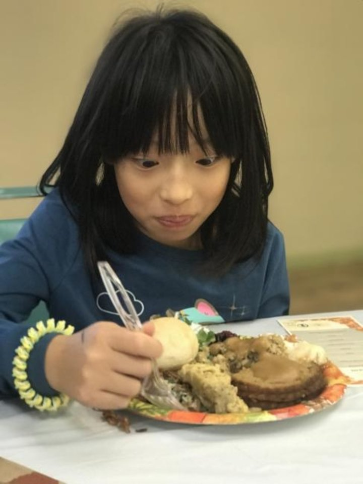 Photo -  Ning Tay, 9 of Edmond, digs into a plate of food at the Community Plant-based Thanksgiving Dinner hosted in northeast Oklahoma City by A Table In The Wilderness. [Carla Hinton/The Oklahoman]