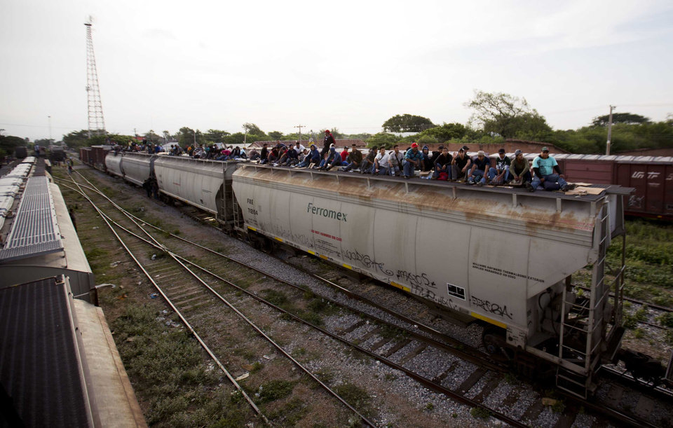 Photo - In this July 12, 2014, photo, Central American migrants ride a freight train during their journey toward the U.S.-Mexico border in Ixtepec, Mexico. Many of the children and teenagers who travelled to the United States recently said they did so after hearing they would be allowed to stay. The U.S. generally releases unaccompanied children to parents or relatives while their cases take years to wend through overwhelmed immigration courts. (AP Photo/Eduardo Verdugo)