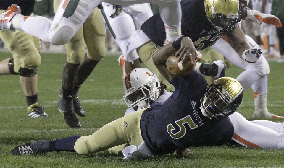 Photo -   Notre Dame quarterback Everett Golson (5) scrambles to the one yard line and is tackled by Miami linebacker Eddie Johnson during the first half of an NCAA college football game at Soldier Field Saturday, Oct. 6, 2012, in Chicago.(AP Photo/Charles Rex Arbogast)