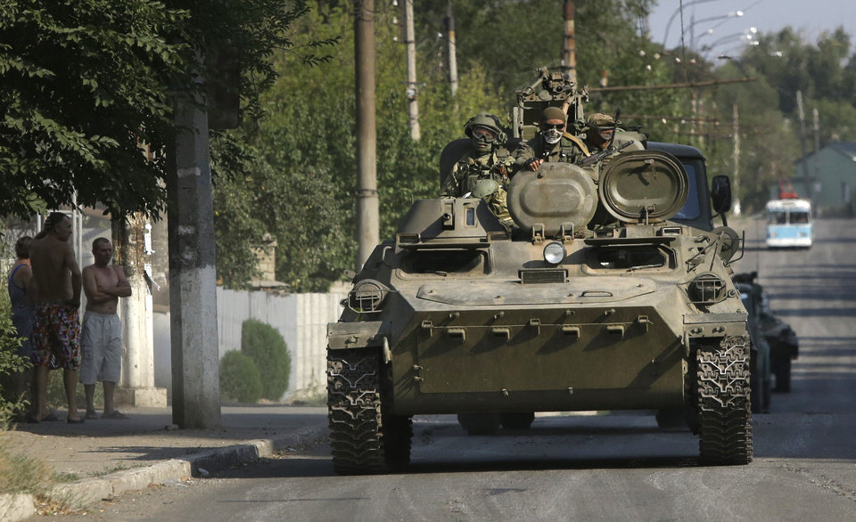 Photo - Pro-Russian rebels ride on an APC in the town of Krasnodon, eastern Ukraine, Sunday, Aug. 17, 2014. A column of several dozen heavy vehicles, including tanks and at least one rocket launcher, rolled through rebel-held territory on Sunday.(AP Photo/Sergei Grits)