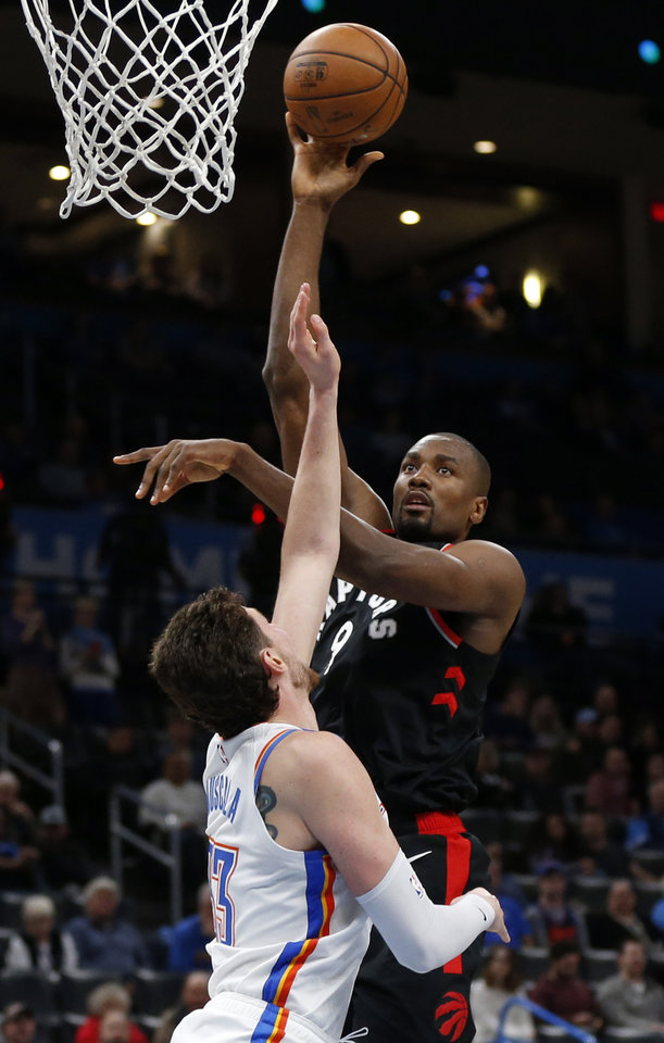 Photo - Toronto's Serge Ibaka (9) shoots over Oklahoma City's Mike Muscala (33) in the fourth quarter during an NBA basketball between the Oklahoma City Thunder and the Toronto Raptors at Chesapeake Energy Arena in Oklahoma City, Wednesday, Jan. 15, 2020. Toronto won 130-121. [Nate Billings/The Oklahoman]