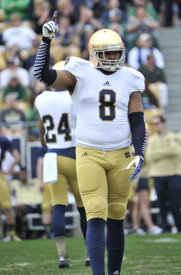 Photo - FILE - In this April 12, 2014, file photo, Notre Dame linebacker Kendall Moore signals during the Blue Gold Game spring NCAA college football game in South Bend, Ind. Notre Dame barred football players KeiVarae Russell, DaVaris Daniels, Ishaq Williams, and Kendall Moore  from practice and games Friday, Aug. 15, 2014, after announcing an investigation into
