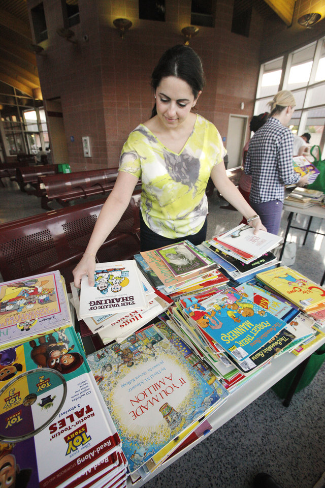 Junior League volunteer Dini Homsey  sets out children's books on a table set up by members of the Junior League of Oklahoma City at the Metro Transit Downtown Transit Center in Oklahoma City Friday, July 20, 2012. The books were given free to bus riders. Photo by Paul B. Southerland, The Oklahoman