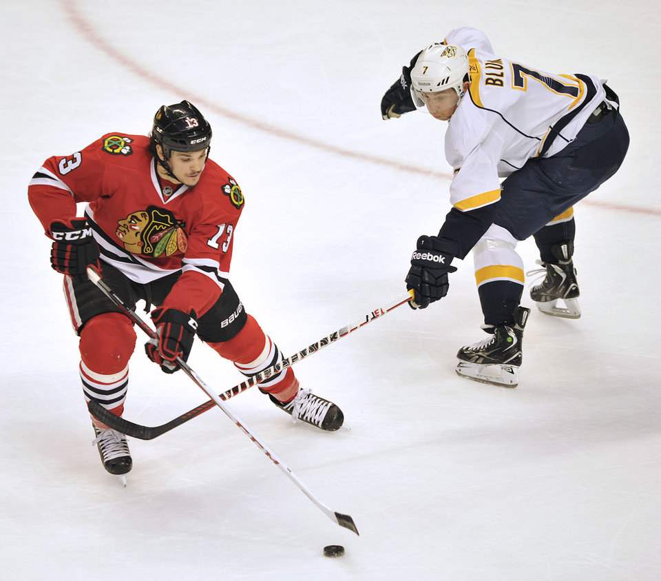 Photo - Chicago Blackhawks' Daniel Carcillo (13) keeps the puck away from Nashville Predators' Jonathon Blum during the second period of an NHL hockey game Monday, April 1, 2013, in Chicago. (AP Photo/Jim Prisching)