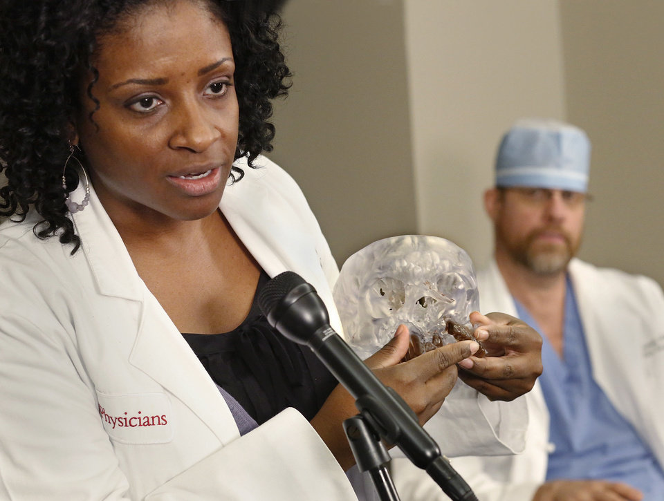Dr. Trinitia Cannon, an ear, nose and throat doctor at OU Medical Center, uses a model of a skull Monday as she and Dr. Jose Sanclement, also an otolaryngologist, discuss the surgical process of reconstructing Taron Pounds� face. Photos by Jim Beckel, The Oklahoman
