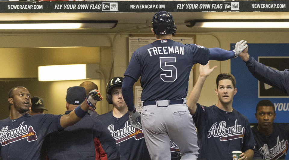 Photo - Atlanta Braves' Freddie Freeman is greeted by teammates after hitting a solo home run off of Milwaukee Brewers' Zach Duke during the eighth inning of a baseball game Tuesday, April 1, 2014, in Milwaukee. (AP Photo/Tom Lynn)