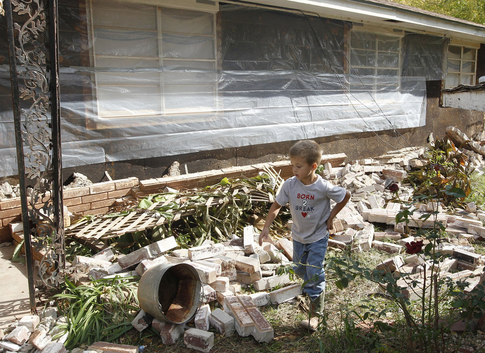 Photo - Five-year-old Logan Devereaux walks past some of the bricks that fell from three sides of this home in Sparks, Okla., Sunday, Nov. 6, 2011, following two earthquakes in less than 24 hours. The home owners have placed plastic around the home to try and protect what is left. (AP Photo/Sue Ogrocki) ORG XMIT: OKSO116