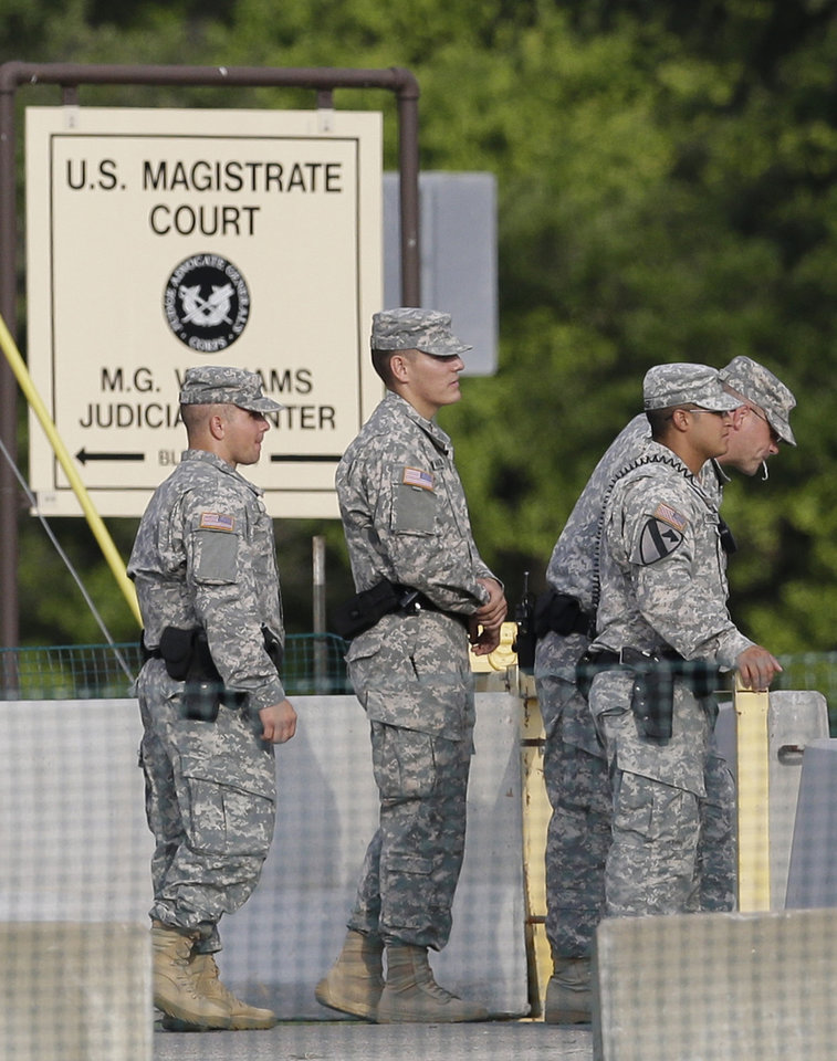 Photo - Soldiers stand guard on the driveway leading to the courthouse holding the the court martial of  Maj. Nidal Malik Hasan Friday, Aug. 23, 2013, in Fort Hood, Texas. Military jurors are deliberating for a verdict against Hasan, on trial for the 2009 shooting rampage at Fort Hood. (AP Photo/LM Otero)