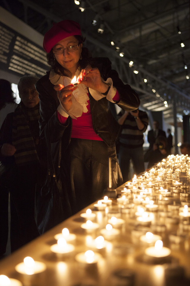 Photo - A woman lights a candle during a ceremony marking International Holocaust Remembrance Day in Russia's first Jewish Museum in Moscow, Russia, Sunday, Jan. 27, 2013. (AP Photo/Alexander Zemlianichenko Jr)
