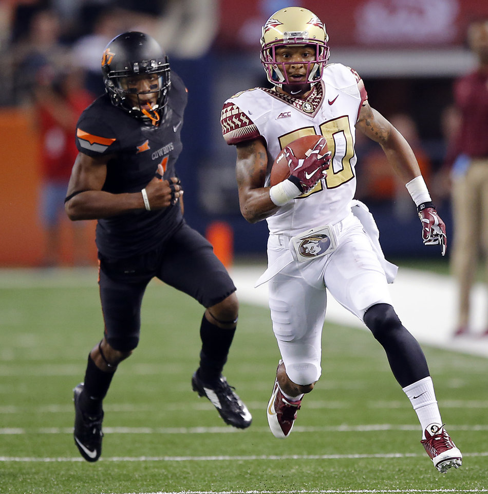 Photo - Florida State's Rashad Greene (80) runs away from Oklahoma State's Kevin Peterson (1) during the college football game between Oklahoma State University (OSU) and Florida State University (FSU) at the AdvoCare Cowboys Classic at AT&T Stadium in Arlington, Texas on Saturday, Aug. 30, 2014. Photo by Chris Landsberger, The Oklahoman