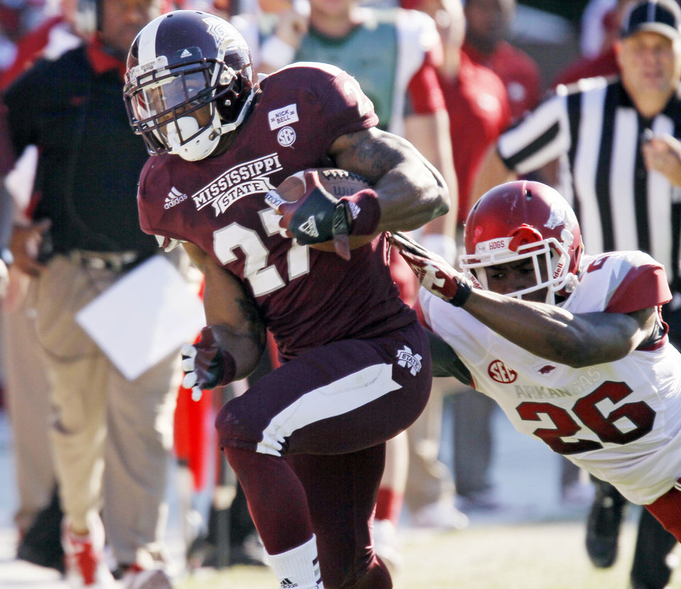 Photo -   Mississippi State running back LaDarius Perkins (27) runs though an attempted tackle by Arkansas safety Rohan Gaines (26) in the fourth quarter of their NCAA college football game in Starkville, Miss., Saturday, Nov. 17, 2012. Mississippi State won 45-14. (AP Photo/Rogelio V. Solis)