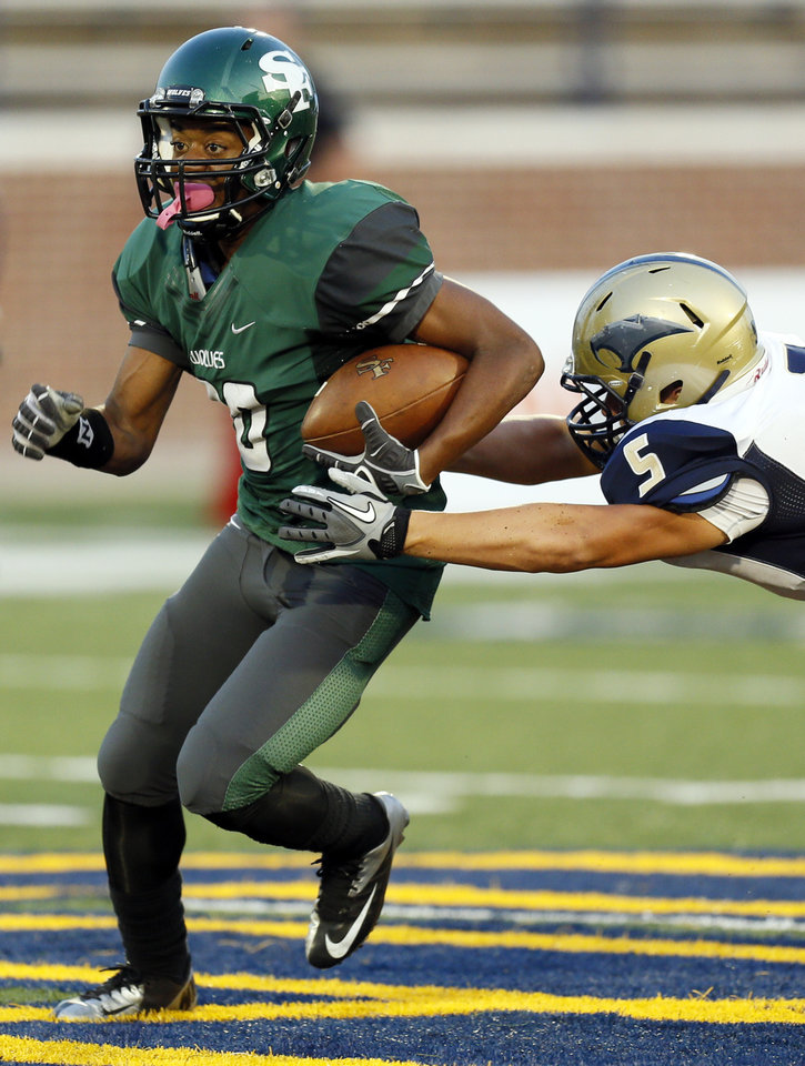 Photo - Southmoore's Jackson Stallings (5) tries to tackle Edmond Santa Fe's Cameron Westbrook (20) during a high school football game between Edmond Santa Fe and Southmoore at Wantland Stadium in Edmond, Okla., Thursday, Sept. 20, 2012. Photo by Nate Billings, The Oklahoman