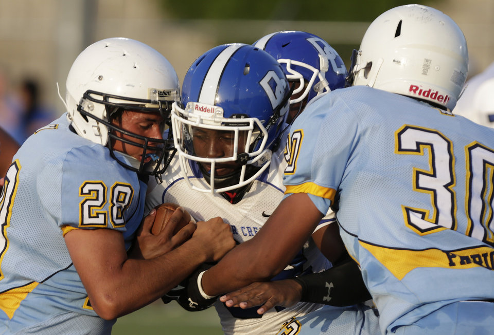 Photo - Deer Creek's Kiwanis Roberts (32) is taken down by Putnam City West's Anthony Montesano (28) during a scrimmage at Putnam City West High School in Bethany, Thursday, Aug. 21, 2014.  Photo by Garett Fisbeck, For The Oklahoman