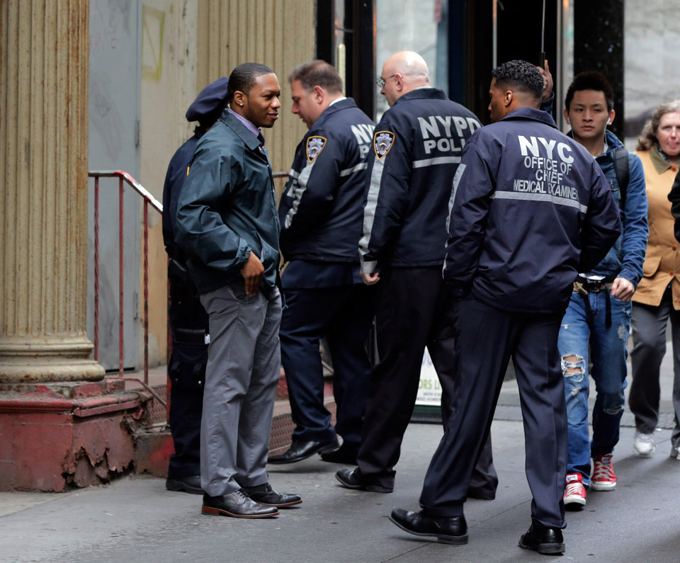 Photo - New York City Police and members of the Office of the Chief Medical Examiner enter a building in Lower Manhattan Monday, April 29, 2013, near the place where a rusted metal part from the wing of a Boeing 767 was found wedged between a mosque and an apartment building on Friday, April 26. Investigators initially thought it was part of the landing gear, because both pieces have similar hydraulics. Authorities believe the aircraft part is from one of the two hijacked planes used in the Sept. 11 attacks on the nearby World Trade Center. The medical examiner's office said Monday it is preparing the site and plans to begin sifting for human remains in the area on Tuesday, April 30. (AP Photo/Richard Drew)