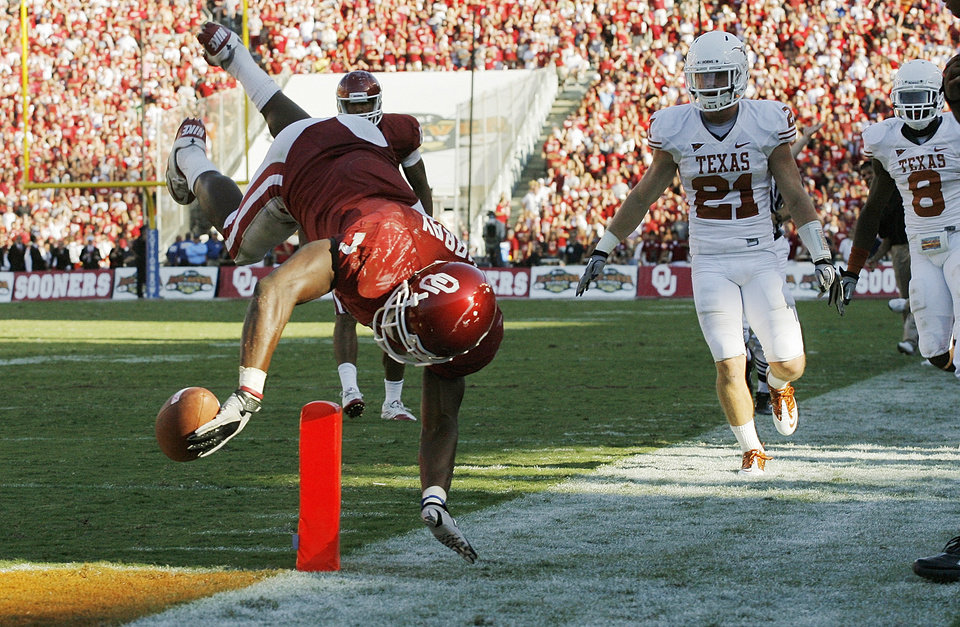 Photo - OU's DeMarco Murray (7) dives for a touchdown in front of Blake Gideon (21) and Chykie Brown (8) of Texas in the fourth quarter during the Red River Rivalry college football game between the University of Oklahoma Sooners (OU) and the University of Texas Longhorns (UT) at the Cotton Bowl on Saturday, Oct. 2, 2010, in Dallas, Texas. OU won, 28-20. Photo by Nate Billings, The Oklahoman