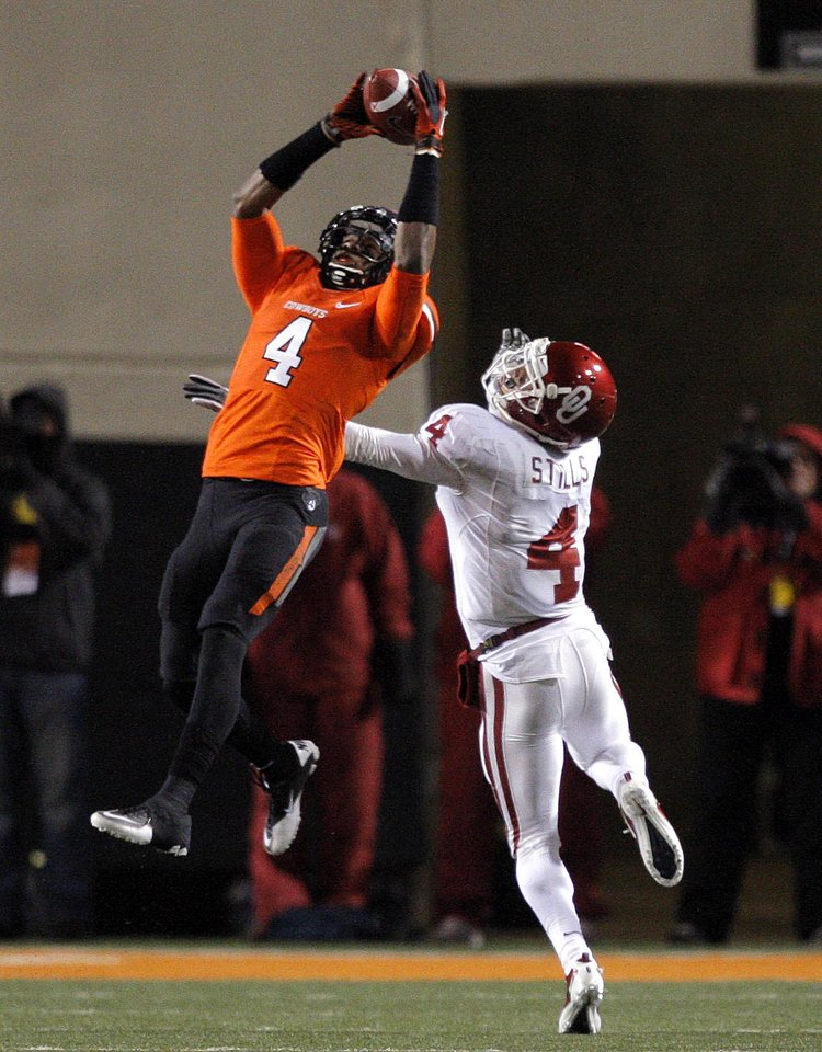 Photo - Oklahoma State's Justin Gilbert (4) makes an interception in front of Oklahoma's Kenny Stills (4) during the Bedlam college football game between the Oklahoma State University Cowboys (OSU) and the University of Oklahoma Sooners (OU) at Boone Pickens Stadium in Stillwater, Okla., Saturday, Dec. 3, 2011. Photo by Sarah Phipps, The Oklahoman