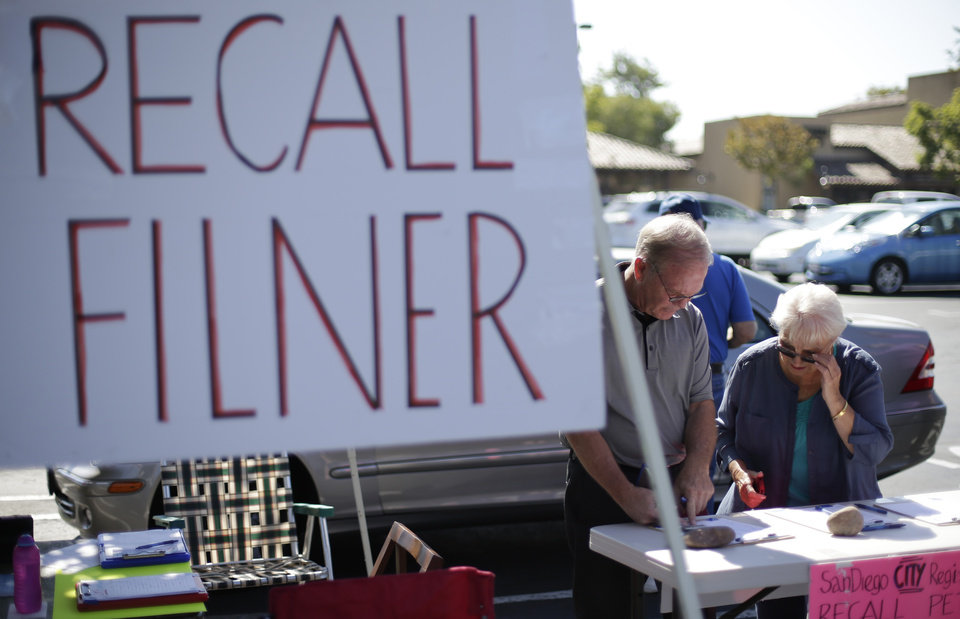 Photo - Greg Timms, left, signs a petition to recall San Diego Mayor Bob Filner, alongside Tana Piontek, right, at a stand set up in the parking lot of a shopping center Wednesday, Aug. 21, 2013, in San Diego.  Pressure is mounting against San Diego's mayor to resign after a sexual harassment lawsuit was filed against him, and the Democratic National Committee plans to vote on a resolution Friday urging him to step down immediately. (AP Photo/Gregory Bull)