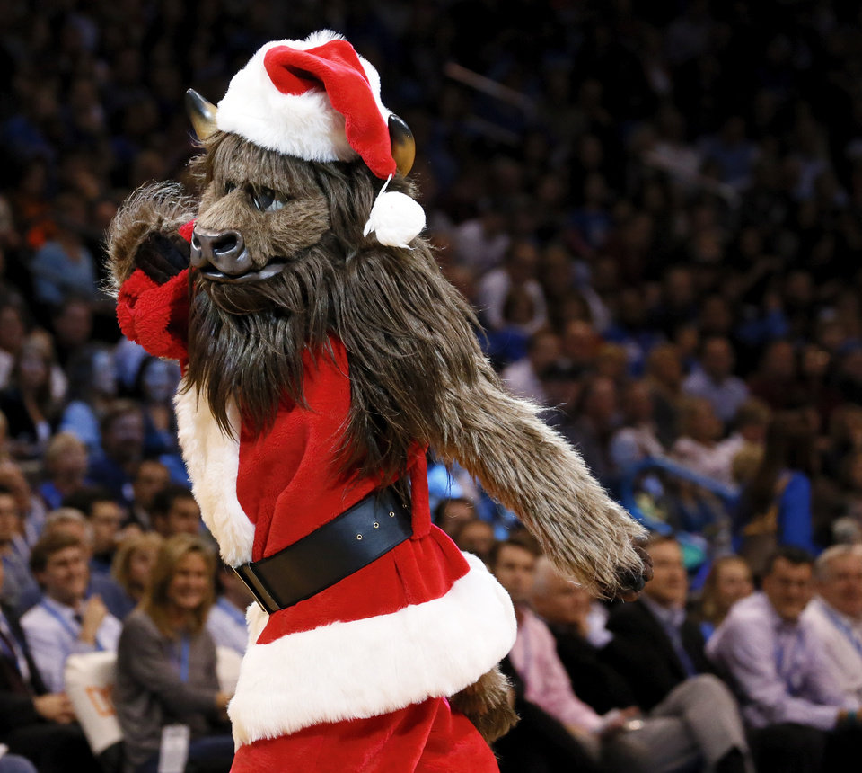 Photo - Thunder mascot Rumble the Bison plays Santa Claus during an NBA basketball game between the Oklahoma City Thunder and the San Antonio Spurs in Oklahoma City Monday, Dec. 17, 2012. Photo by Nate Billings, The Oklahoman
