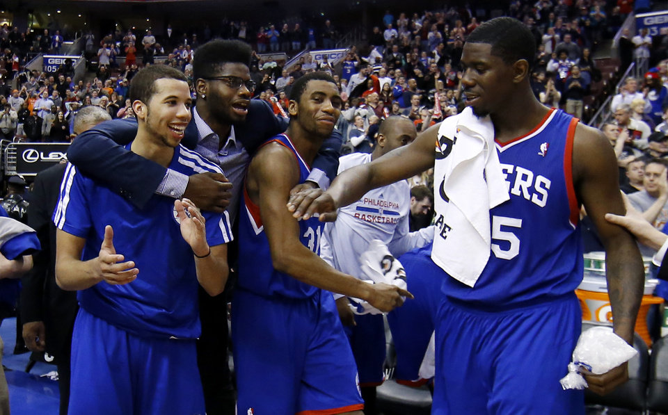 Photo - From left to right, Philadelphia 76ers' Michael Carter-Williams, Nerlens Noel, Hollis Thompson and Henry Sims celebrate in the final seconds of an NBA basketball game against the Detroit Pistons, Saturday, March 29, 2014, in Philadelphia. Philadelphia won 123-98, breaking a 26-game losing streak. (AP Photo/Matt Slocum)