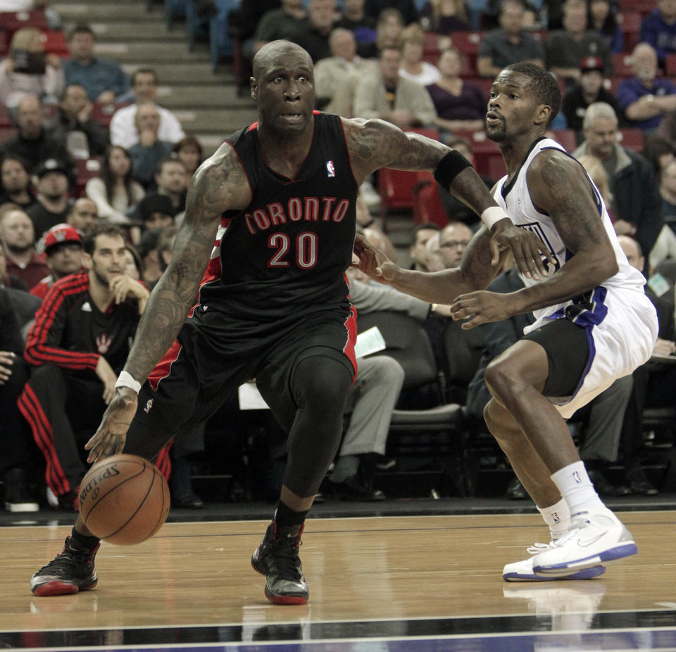 Photo - Toronto Raptors forward Mickael Pietrus, left, drives against Sacramento Kings guard Aaron Brooks during the first quarter of an NBA basketball game in Sacramento, Calif., Wednesday, Dec. 5, 2012.(AP Photo/Rich Pedroncelli)