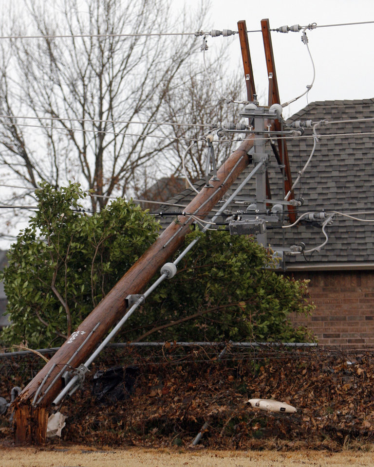 Photo - Power pole down on a house near Sorghum Mill and Kelly, Tuesday , February 10, 2009.  By David McDaniel, The Oklahoman.