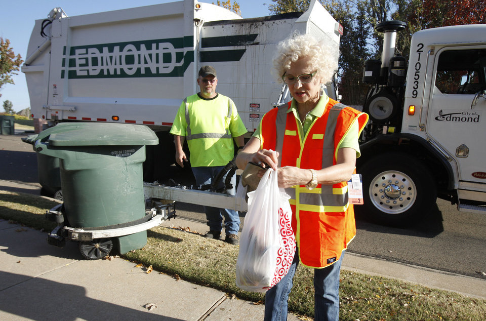 Edmond sanitation truck driver Jeff Whitfield watches former Mayor Saundra Naifeh, president of Edmond Beautiful, tie a bag of trash. PHOTO BY PAUL HELLSTERN, THE OKLAHOMAN. <strong>PAUL HELLSTERN - Oklahoman</strong>