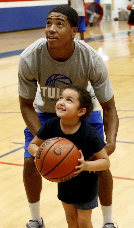Photo - Plaza Tower's pre-schooler Isabelle Delacruz, 5, gets s lift toward the basket from Tulsa University sophomore basketball player Shaq Harrison as former NBA All-Stars Danny Manning, Otis Birdsong, Michael Ray Richardson and others host a basketball clinic for tornado victims on Thursday, June 13, 2013 in Moore, Okla.  Photo by Steve Sisney, The Oklahoman