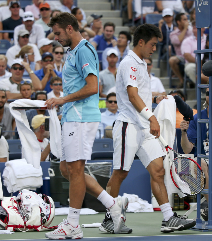 Photo - Stan Wawrinka, of Switzerland, left, and Kei Nishikori, of Japan, cross paths as they walk to their benches during a break between games during the quarterfinals of the 2014 U.S. Open tennis tournament, Wednesday, Sept. 3, 2014, in New York. (AP Photo/Mike Groll)