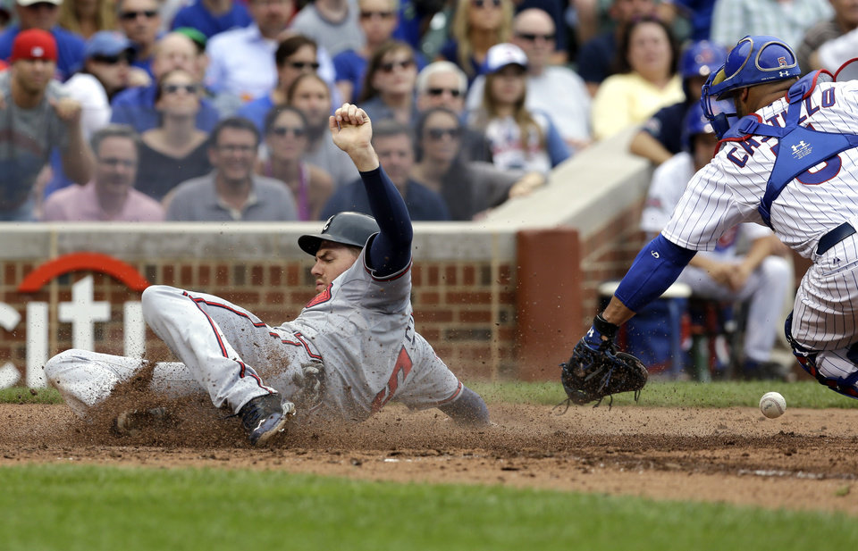Photo - Atlanta Braves' Freddie Freeman, left, scores on a three-run double hit by Justin Upton as Chicago Cubs catcher Welington Castillo tries to catch the ball during the fourth inning of a baseball game in Chicago, Saturday, July 12, 2014. (AP Photo/Nam Y. Huh)