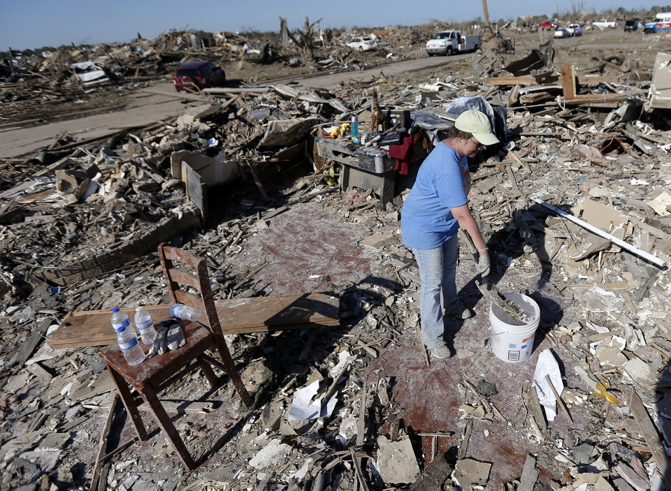 Photo - Vickie Brewer searches for valuables from the home of her boyfriend Kevin Jump in the Plaza Towers neighborhood in Moore, Okla., on Wednesday, May 22, 2013. The home was destroyed by a tornado that struck the area on Monday, May 20, 2013. Photo by Bryan Terry, The Oklahoman