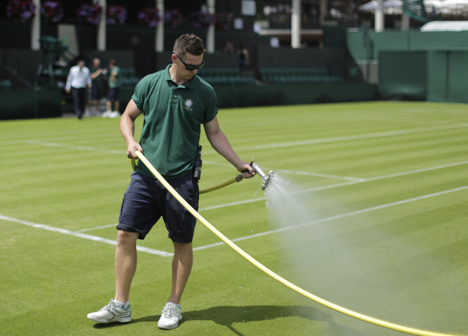 Photo - A member of the ground staff waters a court at the All England Lawn Tennis Championships in Wimbledon, London, Sunday June 22, 2014. The Championships start Monday June 23. (AP Photo/Ben Curtis)