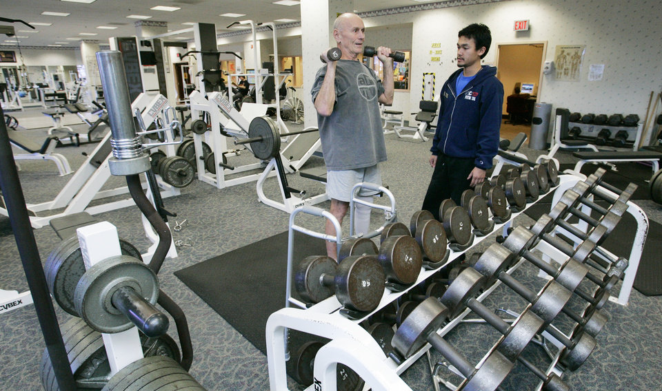 Photo - Federal Employee spouse Bill Boettcher works with trainer Tony Tran inside the U.S. Postal Center hotel's exercise gym Tues. Nov. 24, 2009. The hotel is open to the public and offers many amenities. Photo by Jaconna Aguirre, The Oklahoman.    ORG XMIT: KOD