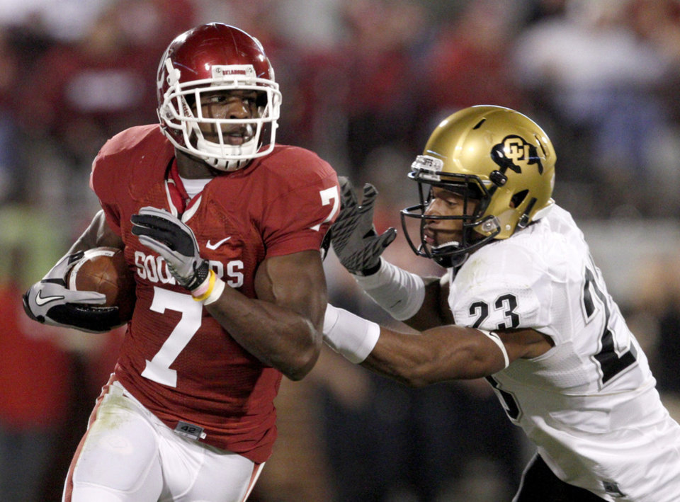 Photo - OU's DeMarco Murray tries to get by Colorado's Jalil Brown during the college football game between the University of Oklahoma (OU) Sooners and the University of Colorado Buffaloes at Gaylord Family-Oklahoma Memorial Stadium in Norman, Okla., Saturday, October 30, 2010. Photo by Bryan Terry, The Oklahoman