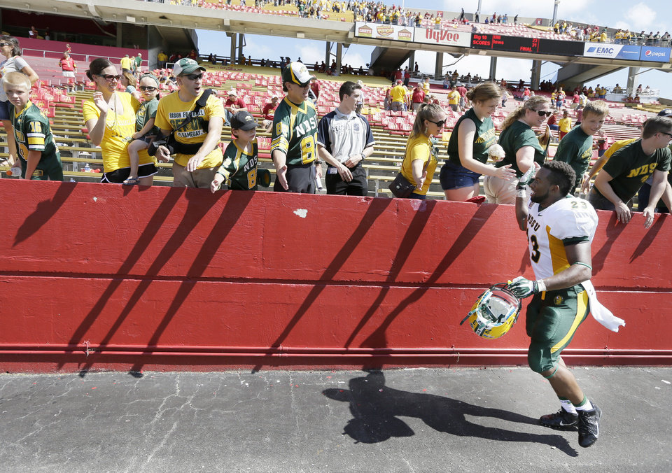Photo - North Dakota State running back John Crockett (23) celebrates with fans after their 34-14 win in an NCAA college football game against Iowa State, Saturday, Aug. 30, 2014, in Ames, Iowa.  (AP Photo/Charlie Neibergall)