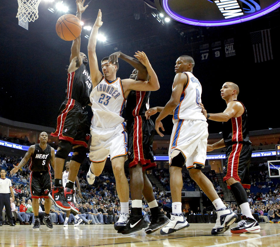 Oklahoma City's Byron Mullens is fouled between Miami's Udonis Haslem, left, and Joel Anthony as Russell Westbrook and Carlos Arroyo watch during an NBA preseason game between the Oklahoma City Thunder and the Miami Heat at the BOK Center in Tulsa, Okla., Wednesday, October 14, 2009. Photo by Bryan Terry, The Oklahoman