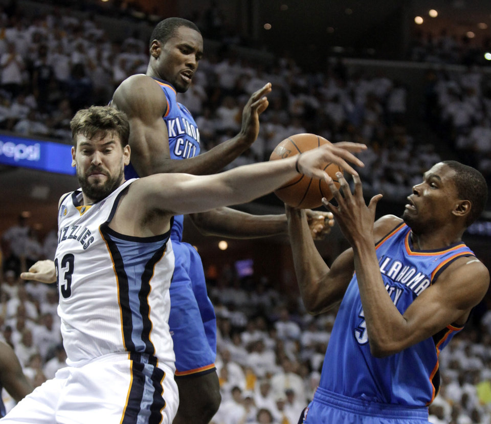 Photo - Memphis Grizzlies center Marc Gasol (33), of Spain, fights for a rebound with Oklahoma City Thunder forward Serge Ibaka, center, and Kevin Durant during the second half of Game 3 of a second-round NBA basketball series on Saturday, May 7, 2011, in Memphis, Tenn. The Grizzlies won 101-93 in overtime to take a 2-1 lead in the series. (AP Photo/Lance Murphey)